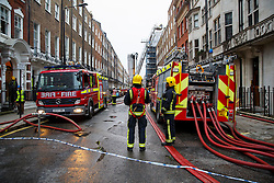 © Licensed to London News Pictures. 30/11/2014. LONDON, UK. Firefighters attending to a large house fire on Wimpole Street in central London after a fire started on the terrace of the five storey building and nine people have been evacuated. Photo credit : Tolga Akmen/LNP