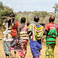 A group of women with sacks in their back and pangas, walk together as they head out to fetch grass and firewood for their homes.