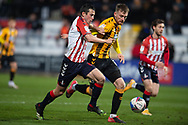 Oldham Athletic midfielder Ben Garrity (6) battles for possession with Robbie Cundy (16) of Cambridge United during the EFL Sky Bet League 2 match between Cambridge United and Oldham Athletic at the Cambs Glass Stadium, Cambridge, England on 5 December 2020.