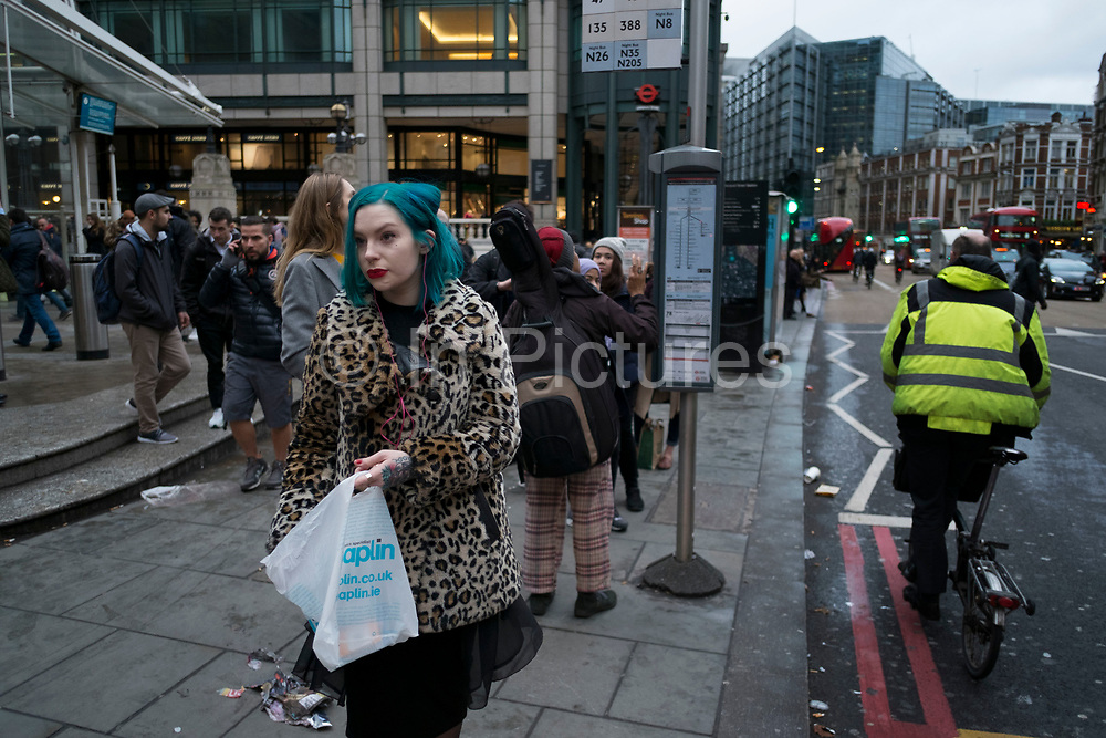 Stylish woman with turquoise hair and tattoos waiting at a bus stop on Bishopsgate in the City of London, England, UK. Very individual unique style with leopard print fur coat, bright red lipstick and pink headphones.