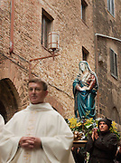 A Roman Catholic procession, with a statue of the Virgin Mary, in the narrow streets of San Gimignano. San Gimignano is a hilltop, medieval town in Tuscany and a UNESCO Heritage Site, Italy