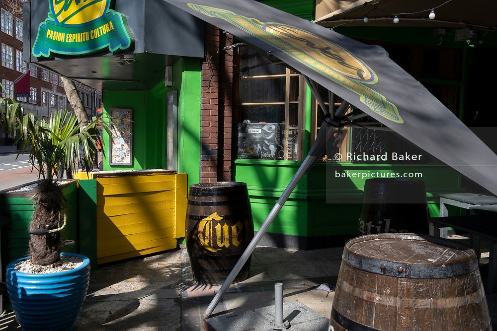 An exterior of a bar where a parasol leans  over on Charing Cross Road during the third lockdown of the Coronavirus pandemic, on 30th March 2021, in London, England.