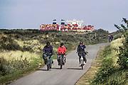 Nederland, Breskens, 5-9-2019Een groot containerschip van rederij MSC is via de Westerschelde op weg naar de haven van Antwerpen . Recreatnen, fietsers, ouderen, fietsen door de duinen langs de zeeuwse kust . Zeeland, zeeuwse,kust, containervervoer,handel,wereldhandel,sancties,economische, containertransport, consumptie, koopgedrag, consumptiegoederen, recreatie,toerisme,toeristen,ouderen,senioren,vergrijzing, aow .Foto: Flip Franssen