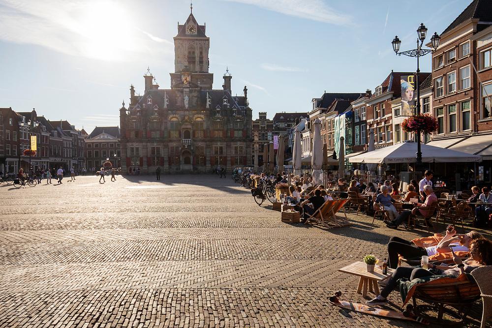 In Delft genieten mensen van het mooie weer op de terrassen op de Markt. In de achtergrond staat het stadhuis.<br /> <br /> In Delft people enjoy the nice weather on the terraces. in the background the town hall.
