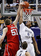 Utah center David Foster (51) is fouled by BYU forward Brandon Davies (0)during the first half of an NCAA college basketball game in Provo, Utah, Saturday, Feb. 12, 2011. (AP Photo/Colin E Braley)