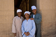 Portrait of three smiling Egyptian men standing in a doorway of the Edfu Temple