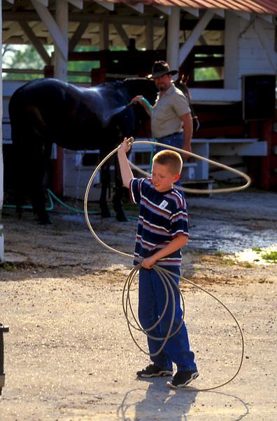 Boy swinging a lasso on a ranch