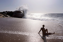 Rear view of a woman relaxing on the beach, Western Province, Sri Lanka
