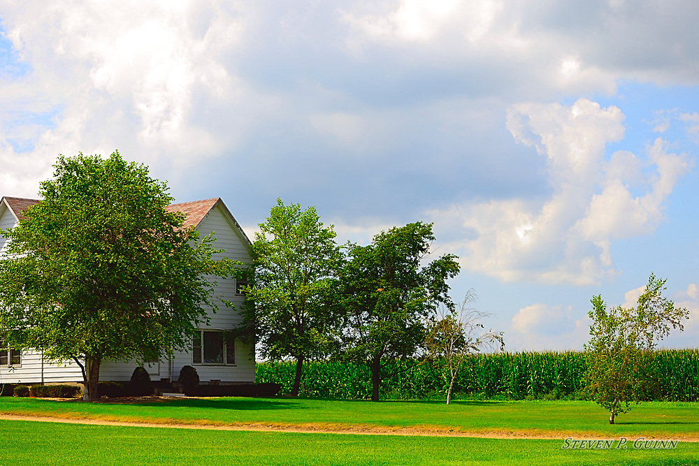 """I captured this landscape image in Rensselaer, Indiana on July 26th, 2016. While I was driving through Rensselaer, Indiana, I came across this house on a farm along a countryside state highway. What drew me to the house was the contrast of the sun shining bright on the side of the house to the shade on the front of the house and the trees. The vivid green colors and subtle details of the foliage and corn field caught my eye because it adds a sense of depth due to the way they are spaced apart. I also like the different patterns that the cumulus cloud formations produced in the sky, making an interesting backdrop. <br /> <br /> Printed on Hahnemühle German Etching paper. Limited to 150 productions per size.<br /> <br /> Framed prints are available in 18"""" x 12"""", 24"""" x 16"""", 30"""" x 20"""", and 36"""" x 24"""" sizes."""