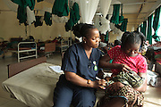 Ward supervisor Tengbeh Dukuly teaches Patience Karkuah, 21, how to breast feed her baby girl, who was born just a few hours ago, at the Redemption hospital in Monrovia, Montserrado country, Liberia  on Wednesday April 4, 2012.