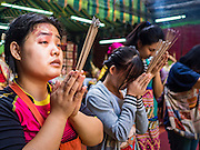 """21 DECEMBER 2015 - BANGKOK, THAILAND:  People pray during the rededication of a community Buddhist shrine in Pak Khlong Talat, also called the Flower Market. The market has been a Bangkok landmark for more than 50 years and is the largest wholesale flower market in Bangkok. A recent renovation resulted in many stalls being closed to make room for chain restaurants to attract tourists. Now Bangkok city officials are threatening to evict sidewalk vendors who line the outside of the market. Evicting the sidewalk vendors is a part of a citywide effort to """"clean up"""" Bangkok.      PHOTO BY JACK KURTZ"""