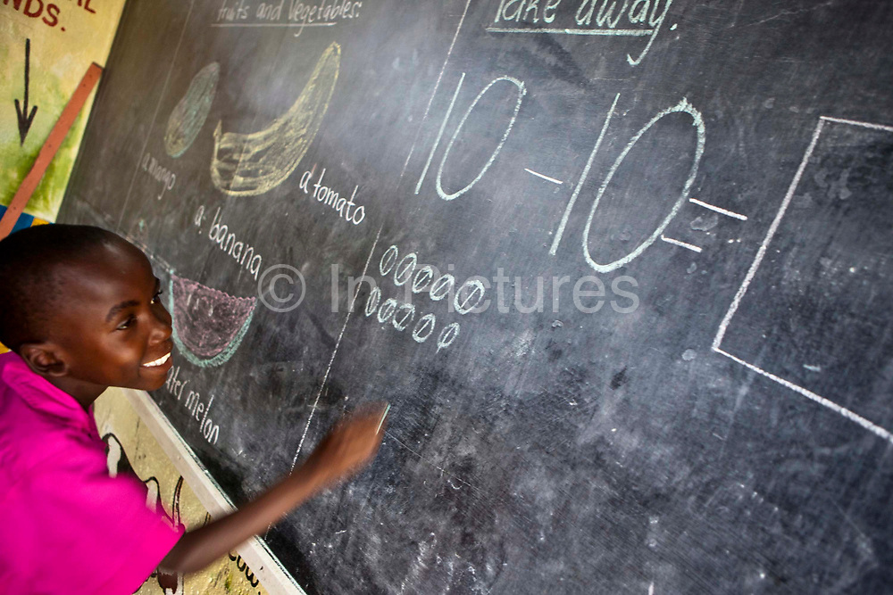 A child from K3 works out a math question on the blackboard. Children attend the kindergarten school to learn a variety of subjects during lessons at the Wema Centre, Mombassa, Kenya. Wema is a NGO organisation in Kenya that provides rehabilitation programs for street children; poor, disadvantaged youth; and, orphaned and vulnerable children affected by poverty. Emotional support and education enables the children reintegration back into society.