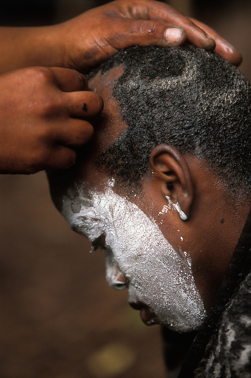 A young Xhosa initiate's head is shaved the day before returning home after one month in seclusion in a special initiation camp. December 2006 in Knysna, South Africa. The boy is going through the traditional Xhosa male initiation rite. He has been circumcised, and his face is painted white to ward off attacks by witches.