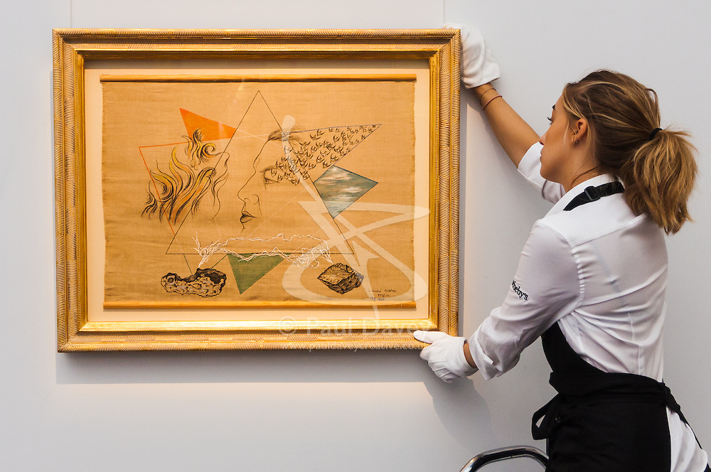 Sotheby's, Mayfair, London, November 7th 2014. Several outstanding examples of Czech avant-garde art from the Roy and Mary Cullen collection are to be auctioned by Sotheby's on November 12th. PICTURED: A Sotheby's worker straightens Toyen's Portrait of Andre Breton, which is expected to fetch between £120,000 to 180,000.