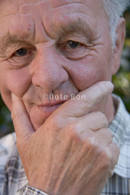 an senior man who his holding his chin with his hand