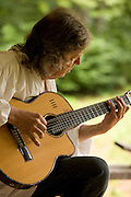 A North Carolina guitar maker sits on his front porch in Morganton, playing one of his guitars.