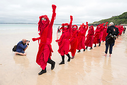 © Licensed to London News Pictures; 11/06/2021; St Ives, Cornwall UK. G7 summit in Cornwall. XR's Red People process on Porthminster Beach at a protest by Extinction Rebellion in St Ives on the first day of the G7 summit. Photo credit: Simon Chapman/LNP.