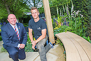 Matthew Keightley (r) and Tom Stimpson   MBE. RAF Veteran on the Hope on the Horizon garden.  The<br /> 'Hope on the Horizon' garden in aid of Help for Heroes: produced by building and landscaping firm Farr and Roberts', making their debut; designed by Matthew Keightley (29), as a result of his brother Michael's involvement with the armed forces, having served on four tours to Afghanistan and due for his fifth this year; and sponsored by the David Brownlow charitable foundation. The garden layout is based on the shape of the Military Cross, the medal awarded for extreme bravery. Granite blocks will represent the soldiers' physical wellbeing and the planting represents their psychological wellbeing at various stages of their rehabilitation. Both evolve through the garden from a rough, unfinished, over-grown beginning through to a perfectly sawn, structured end. An avenue of hornbeams draws the attention through the entire garden to a sculpture resembling a hopeful horizon; a reminder to the soldiers that they all have a bright future ahead. As well as areas to recline and reflect, the garden offers focal points all the way through. Cool, calming colours are used throughout, helping to emphasise the fact that it will be a serene, contemplative space. After the Show, the garden will be moved and set within the grounds at Help for Heroes Recovery Centre at Chavasse VC House in Colchester, Essex. The garden will offer a serene, peaceful haven to contemplate and inspire a bright future and to support the challenging journey to recovery. The Chelsea Flower Show 2014. The Royal Hospital, Chelsea, London, UK