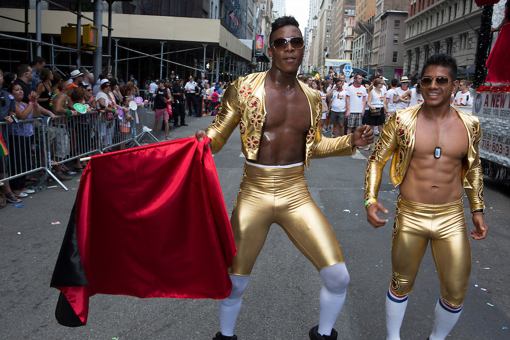 Two men wear gold lamé matador outfits, and one waves a red cape.