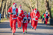 Coming down the avenue from the banstand for the first time - 2000 Santas of all ages take part in the annual Santa Run in Battersea Park to support Noah's Ark Children's Hospice.
