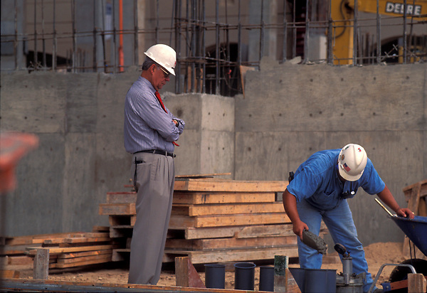 Stock photo of Dionel Aviles, founder and president of Aviles Engineering Corporation, observes a workman preparing a concrete test.