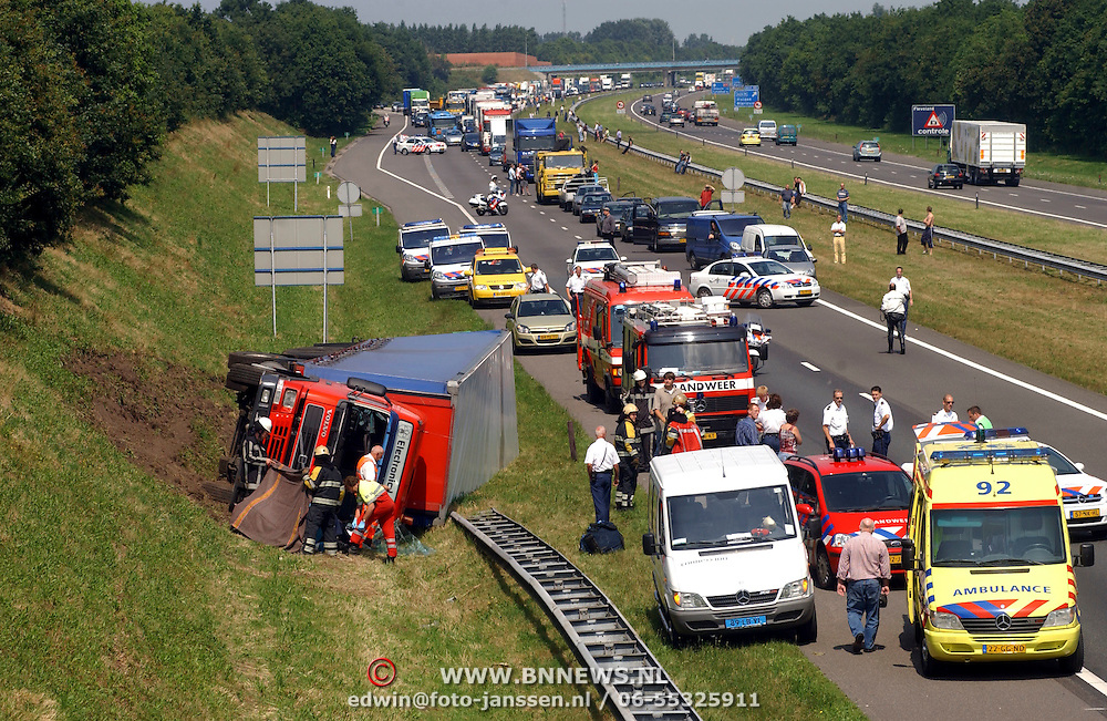 NLD/Blaricum/20050711 - Gekantelde vrachtwagen met gewonde chauffeur snelweg A27 ter hoogte Blaricum.file, chaos, verkeer, ambulance, brandweer, hulp, hulpverlening,