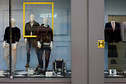 Coincidence of yellow frames in shop window next to yellow fire hydrant sign outside retail business in the City of London. Meanswear on male mannequins are displayed in the window of this London shop - casual more than formal - and we see the obvious connection between the yellow theme of the suares in this urban landscape.