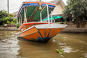 "17 NOVEMBER 2012 - BANGKOK, THAILAND:  A river taxi on a khlong or canal in the Thonburi section of Bangkok. Bangkok used to be known as the ""Venice of the East"" because of the number of waterways the criss crossed the city. Now most of the waterways have been filled in but boats and ships still play an important role in daily life in Bangkok. Thousands of people commute to work daily on the Chao Phraya Express Boats and fast boats that ply Khlong Saen Saeb or use boats to get around on the canals on the Thonburi side of the river. Boats are used to haul commodities through the city to deep water ports for export.    PHOTO BY JACK KURTZ"