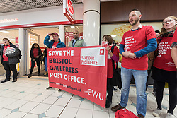 © Licensed to London News Pictures. 01/12/2018. Bristol, UK. Bristol's elected Mayor MARVIN REES (middle behind banner) at the Save Our Post Offices campaign event at Bristol's main post office which under threat of closure in The Galleries Shopping Centre. Members of the Communication Workers Union (CWU) supported by Bristol Trades Union Council were joined by Bristol's elected Mayor Marvin Rees to campaign against the proposed closure. This is part of a national campaign day, Saturday 01 December, to save Crown Post Offices from closure. Bristol's main Post Office in The Galleries shopping centre is on the list of regional closures along with the main Post Offices in Bath and Gloucester, with services due to be transferred to post office counters in branches of WH Smiths under a franchise arrangement. And in Kingswood the post office which moved to WH Smith last year would transfer to be operated directly by WH Smiths with Post Office workers becoming Smiths' employees. It is feared while fully trained Post Office counter staff should be moved across and retain their £12-an-hour salaries, any new staff would be employed by WHSmith at the minimum wage. The campaign has been launched by the CWU in response to the announcement that 74 Crown offices are to be franchised (privatised) to high-street retailer WH Smith – a move which will impact some 800 jobs and drastically cut services to communities. Photo credit: Simon Chapman/LNP