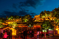 Illuminated wooden houses surround Square Market, the main plaza of Old Town (Dayan) in Lijiang, Yunnan Province, China. The Old Town is a UNESCO World Heritage Site.