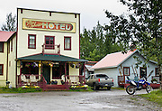 """Ma Johnson's Hotel hosts visitors in historic McCarthy. McCarthy and nearby Kennecott Mines National Historic Landmark are nestled under the glacier-clad Wrangell Mountains within Wrangell-St. Elias National Park and Preserve, Alaska, USA. Old mine buildings, artifacts, and colorful history attract summer visitors. Remote McCarthy is connected to Chitina via the McCarthy Road spur of the Edgerton Highway. At the east end of McCarthy Road, visitors must park their vehicle and walk across the footbridge to McCarthy. From McCarthy, a privately-operated shuttle takes visitors 5 miles to Kennecott. After copper was discovered between the Kennicott Glacier and McCarthy Creek in 1900, the Kennecott town, mines, and Kennecott Mining Company were created and named after the adjacent glacier. Kennicott Glacier and River had previously been named after Robert Kennicott, a naturalist who explored in Alaska in the mid-1800s. The corporation and town stuck with a mistaken spelling of """"Kennecott"""" with an e (instead of """"Kennicott"""" with an i). Partly because alcoholic beverages and prostitution were forbidden in the company town of Kennecott, the neighboring town of McCarthy grew quickly to provide a bar, brothel, gymnasium, hospital, and school. The Copper River and Northwestern Railway reached McCarthy in 1911 to haul over 200 million dollars worth of ore 196 miles to the port of Cordova on Prince William Sound. By 1938, the worlds richest concentration of copper ore was mostly gone, the town was mostly abandoned, and railroad service ended. Not until the 1970s did the area began to draw young people for adventure and the big money of the Trans Alaska Pipeline project. Declaration of Wrangell-St. Elias National Park in 1980 drew adventurous tourists who helped revive McCarthy with demand for needed services. Wrangell-St. Elias National Park and Preserve (the largest National Park in the USA) is honored by UNESCO as a World Heritage Site."""