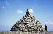 Young man sitting on stone cairn at summit of  Dunkery Beacon, highest point in Exmoor national park, Somerset, England 1,705 ft 520 metres, 1967