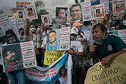 """Family members demanding justice hold a protest outside the attorney general's office, thrusting aloft photos of their loved ones, who they say were disappeared by the attorney general's masked police. """"A criminal group took over the institutions of the state of Nayarit for six years,"""" said Rodrigo González Barrios, spokesman for the truth commission."""