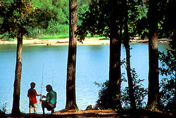 Stock photo of the silhouette of a father and son fishing at a lake
