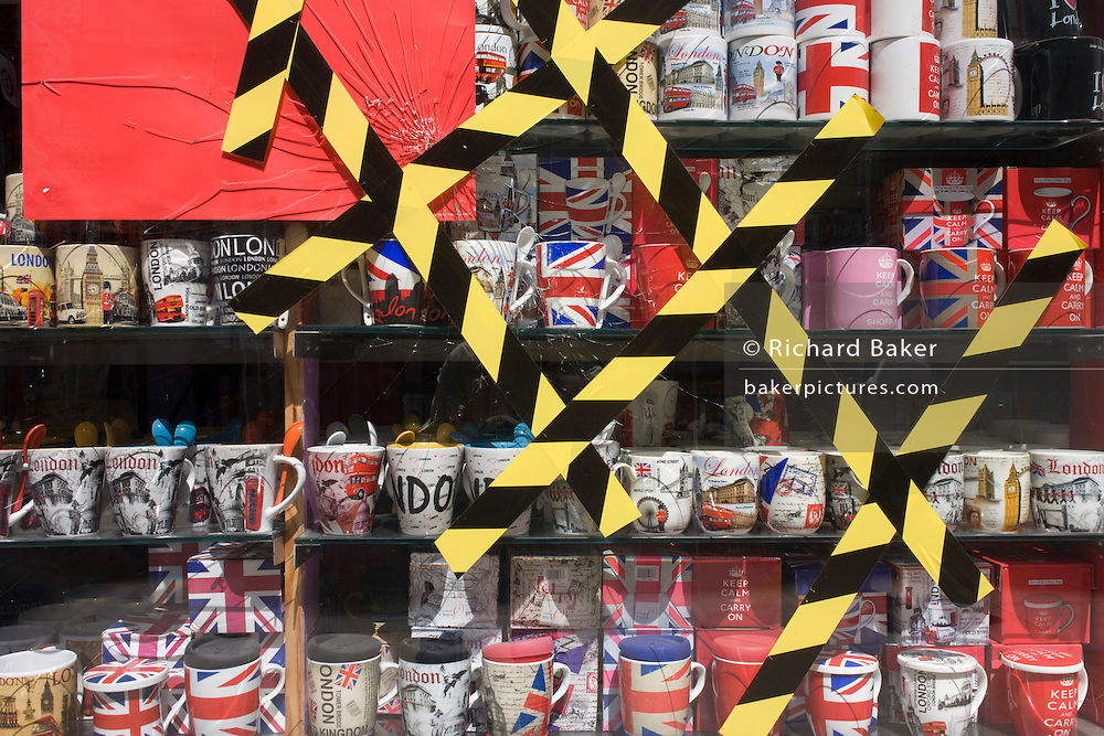 Cracked glass in the windnow of a tourist souvenir shop has been selaed over with striped diagonal tape.