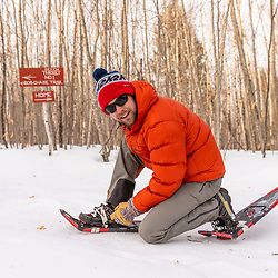 A man putting on snowshoes at Loon Echo Land Trust's Bald Pate Mountain Preserve in South Bridgton, Maine.