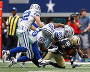 New Orleans Saints wide receiver Marques Colston (12) is tackled by a gang of Dallas Cowboys at Cowboys Stadium in Arlington, Texas, on December 23, 2012.  (Stan Olszewski/The Dallas Morning News)