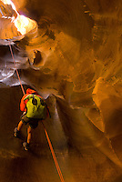A young man rappels while canyoneering in Pine Creek Canyon.  Zion National Park, Utah.