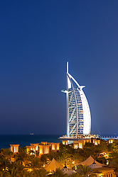 View of resort hotels at night at Madinat Jumeirah and Burj al Arab hotel to rear in Dubai in United Arab Emirates