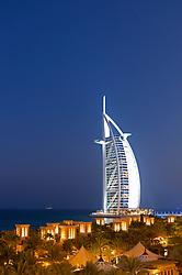 View of resort hotels at night at Madinat Jumeirah and Burj al Arab hotel to rear in Dubai in United Arab Emirates