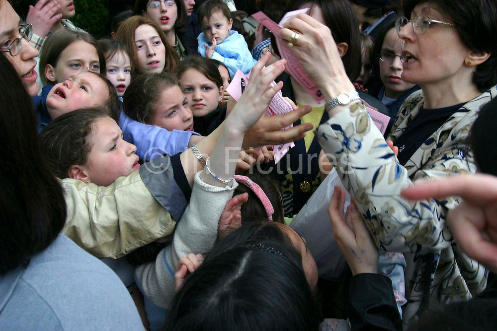 Women and children struggle to get vouchers for free kosher ice cream, the only kosher ice cream van in the UK visiting a community event in Allen Gardens, Stamford Hill to celebrate Lag B'Omer. Lag B'Omer is the holiday celebrating the thirty-third day of the (counting of the) Omer. Jews celebrate it as the day when the plague that killed 24,000 people ended in the holy land (according to the Babylonian Talmud). Other sources say the plague was actually the Roman occupation and the 24,000 people died in the second Jewish – Roman war  (Bar Kokhba revolt of the first century).  Bonfires (used as signals in wartime) are symbolically lit to commemorate the holiday of Lag'B'Omer.