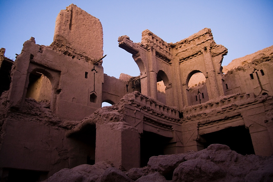 The setting sun illuminates the crumbling walls  of Ait Bounou, an ancient kasbah, or fortified village, in the Moroccan Sahara on November 8, 2007. The town is quickly falling into ruin as the inhabitants flee the drying well and the advancement of the dunes expedited by a 16-year drought and the damming of the Draa River.