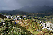 With dark skies approaching over distant mountains, a walker climbs a public footpath, once an industrial track for the slate mining industry, on 5th October 2021, in Blaenau Ffestiniog, Gwynedd, Wales. The derelict slate mines around Blaenau Ffestiniog in north Wales were awarded UNESCO World Heritage status in 2021. The industry's heyday was the 1890s when the Welsh slate industry employed approximately 17,000 workers, producing almost 500,000 tonnes of slate a year, around a third of all roofing slate used in the world in the late 19th century. Only 10% of slate was ever of good enough quality and the surrounding mountains now have slate waste and the ruined remains of machinery, workshops and shelters have changed the landscape for square miles.