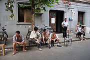 Men relaxing on Dong Tai Road, Dongtai Lu, street market in Shanghai, China. This small area, dedicated to antiques is lined with shops and the streets covered with stalls selling artifacts from Shanghais past. There are some genuine Chinese antiques which can be very expensive. But there are also a lot of fakes for sale too, like these figures. Usually snapped up by tourists who are under the impression they are getting a bargain.