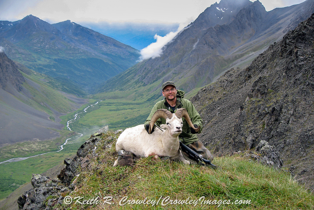 Keith Crowley with his ram in a scenic Alaskan valley.