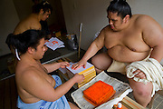 Takeuchi Masato (ring name Miyabiyama) makes a handprint during a break at pre-tournment practice in Nagoya,  Japan.  The prints are given to fans and sponsors. (Takeuchi Masato is featured in the book What I Eat, Around the World in 80 Diets.) The caloric value of his typical day's worth of food in June was 3500 kcals.  He is one of the largest of the Japanese sumos and would probably have moved up even further in the ranks had he not suffered a severe shoulder injury. He is only just now returning to matches. MODEL RELEASED.