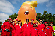 The Trump Baby sitting team dressed in red boiler suits in front of the six metre high inflatable TrumpBaby before his flight above Parliament Square, London, United Kingdom. 13th July 2018.