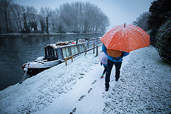 © Licensed to London News Pictures. 10/12/2017. Reading, UK. A man and his daughter walk in the fresh snow next to the River Thames near Reading, Berkshire, as parts of the south east of England are blanketed with snow for the first time this winter. Photo credit: Peter Macdiarmid/LNP