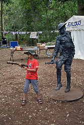 Latitude Festival, Henham Park, Suffolk, UK July 2018. Boy mimicking a rifle next to WW1 statue