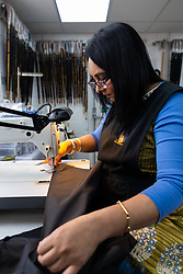 A seamstress sews the hem of an umbrella cover. Craftspeople at Fox Umbrellas Ltd, a company in Croydon, Surrey, that has been going for over 150 years hand build quality umbrellas. Croydon, Surrey, March 06 2019.
